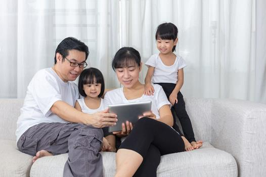 Family of four with two young children, sitting on a couch and looking at an iPad screen.